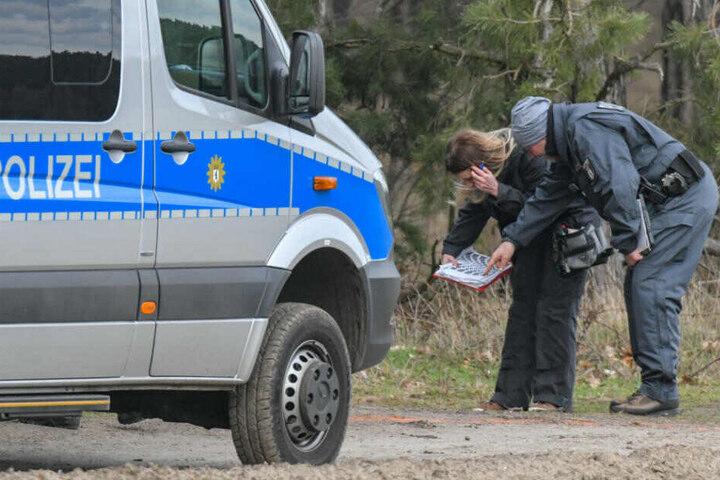 Beamte der Kriminalpolizei stehen während der Suche nach der vermissten Rebecca an einem Waldgebiet im Landkreis Oder-Spree und nehmen einen Gipsabdruck einer Reifenspur.