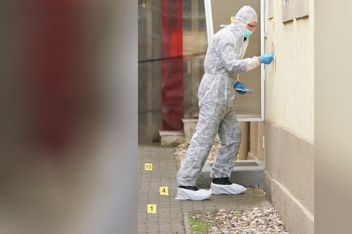 Ein Mitarbeiter der Spurensicherung an der Hauswand des benachbarten Gebäudes, in dem die Familie wohnte.