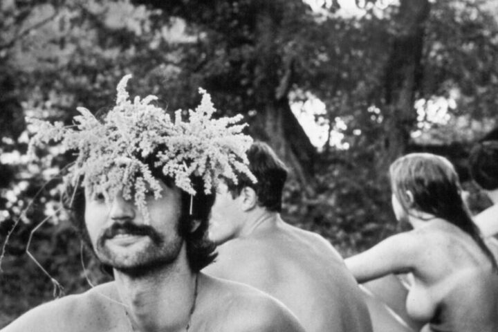 Einige unbekleidete Besucher sitzen im August 1969 beim Musikfestival Woodstock in Bethel.