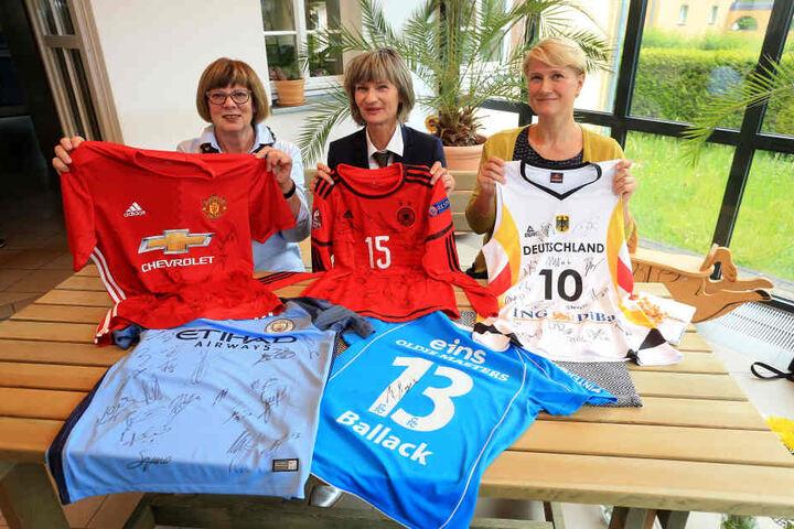 Oberbürgermeisterin Barbara Ludwig versteigert auf eBay fünf Trikots. Der Erlös geht an Inge Oehme (F.l.) vom Elternverein krebskranker Kinder und Tina Kießling von der KiSS-Kindersportschule (F.r.)