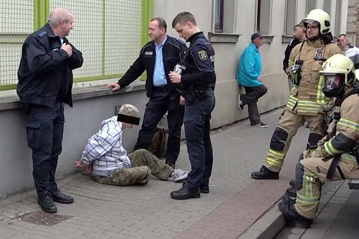 Die Tatverdächtige sitzt in Handschellen auf dem Boden vor dem Mietshaus, in dem sie gezündelt haben soll.