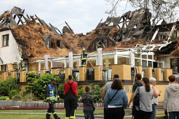 Urlauber und Feuerwehrleute betrachten das Hotelgebäude.