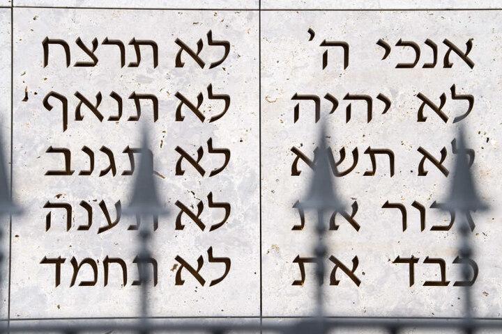 Ein Zaun steht in Stuttgart vor der Synagoge der Israelitischen Religionsgemeinschaft, auf deren Wand im Hintergrund die ersten Worte der zehn Gebote in hebräisch geschrieben sind.