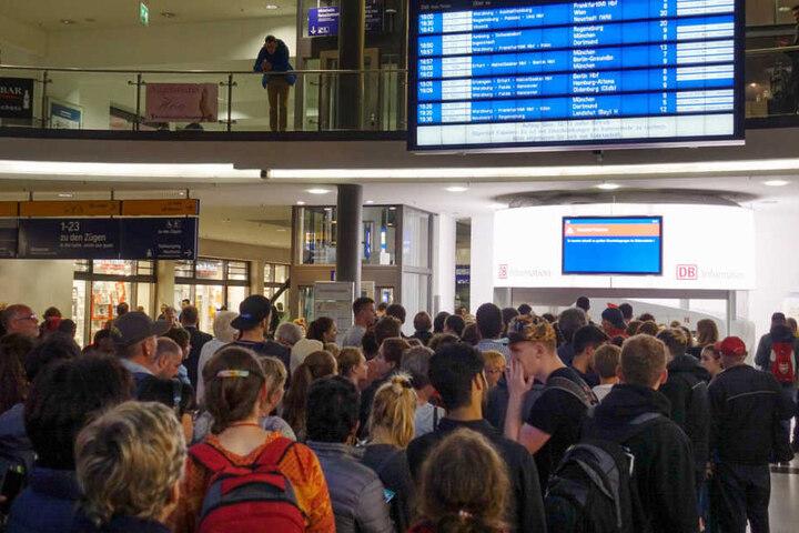 Reisende schauen auf einen Monitor im Hauptbahnhof von Nürnberg auf dem bedingt durch Sturmtief Fabienne auf Einschränkungen im Bahnverkehr hingewiesen wird.