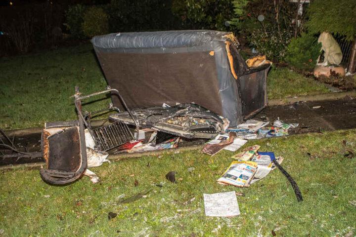 Ein verbranntes Sofa sowie weitere Gegenstände wurden auf den Rasen hinter dem Haus geworfen.