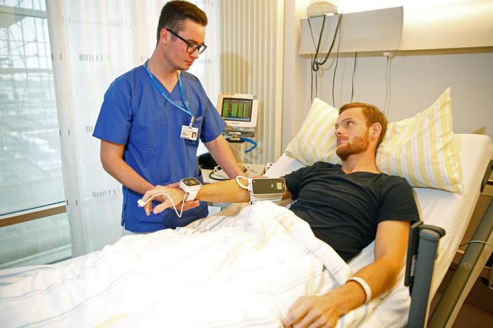 Entlastung des Pflegepersonals: Anstatt selbst aller fünf Minuten die  Vitalfunktionen zu messen, hat Pfleger Lukas Großmann (24) Patient Fabian (26)  die Überwachungs-Manschette angelegt, welche das übernimmt.