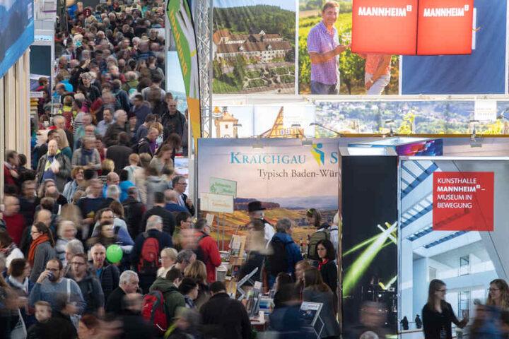 Besucher gehen am ersten Tag der Reisemesse CMT durch eine Halle der Messe Stuttgart.
