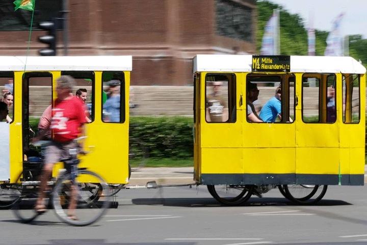 Fahrradfahrer mit einer nachgebildeten Straßenbahn fahren bei der Berliner Fahrradsternfahrt den Großen Stern entlang