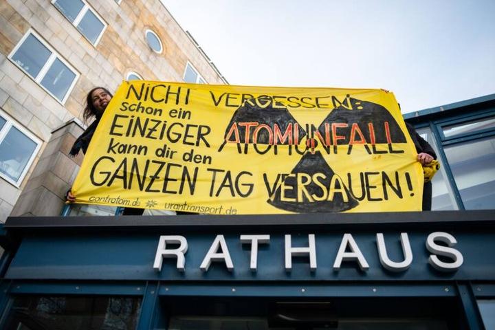 Zwei Demonstrantinnen rollten ein Transparent auf dem Vordach des Rathauses aus.