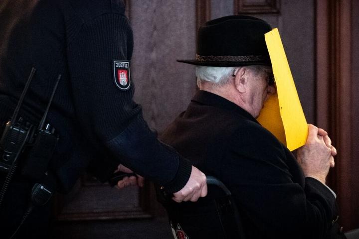 Der Angeklagte wird in einer Pause in einem Rollstuhl aus dem Gerichtssaal gebracht.