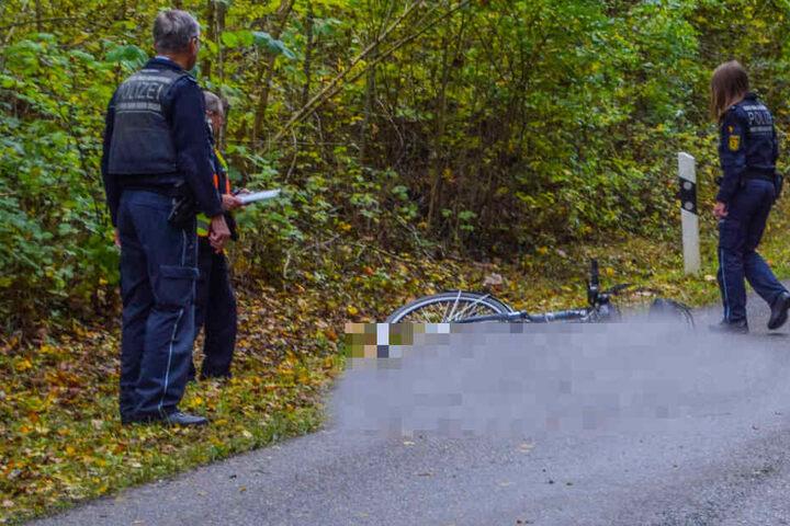 Polizisten blicken auf die Unfallstelle.