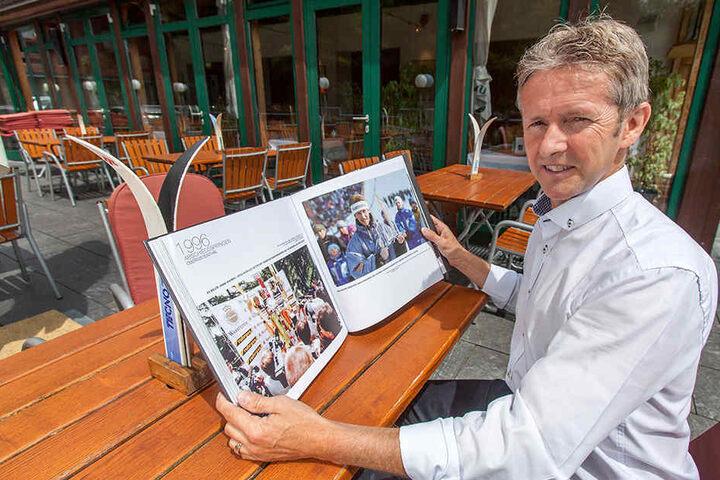 """Der ehemalige Skipringer Jens Weißflog blättert in seinem Buch """"Bilder meines Lebens""""."""