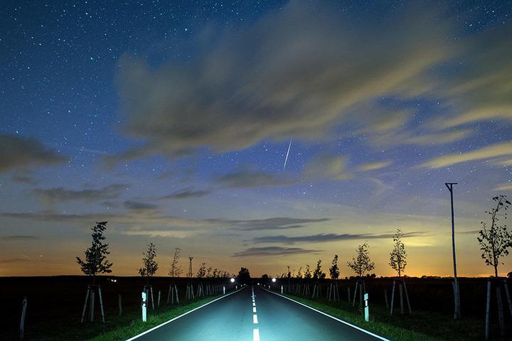 Eine Sternschnuppe leuchtet am Nachthimmel über eine Landstraße nahe Lietzen im Landkreis Märkisch-Oderland (Brandenburg).