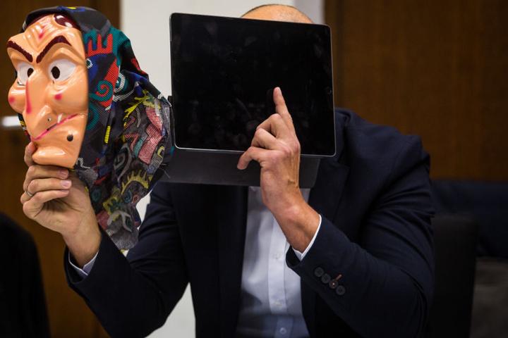 Ein Angeklagter sitzt auf seinem Platz im Amtsgericht, hält sich ein Tablet vor das Gesicht und in der anderen Hand hält er eine Hexenmaske.