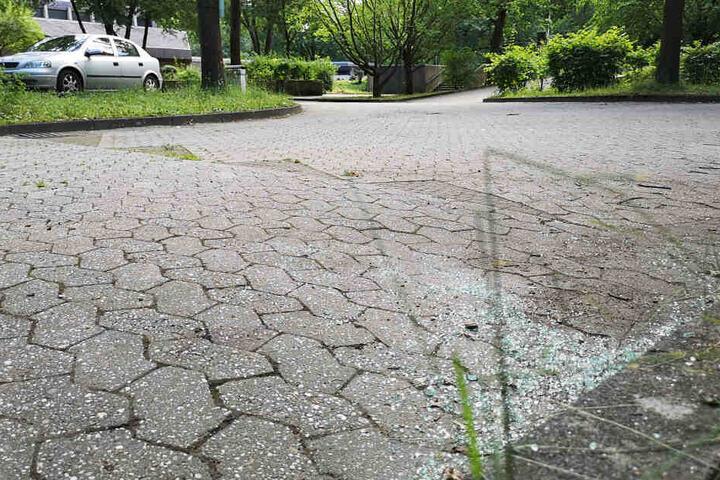 Glasscherben liegen auf einem Parkplatz eines Friedhofes. Hier ereignete sich im Juni 2019 die Tat.