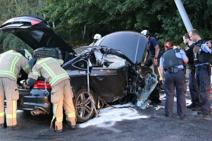 Polizei und Feuerwehr betrachten den Wagen.