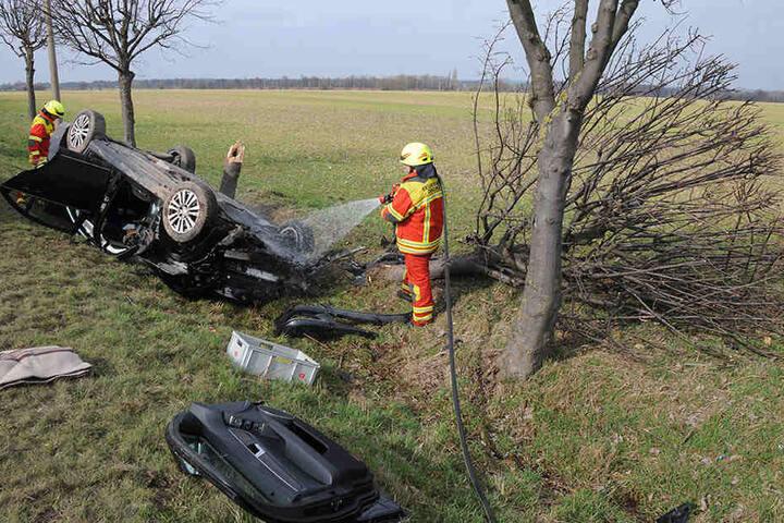Einsatzkräfte der Feuerwehr an der Unfallstelle. Auf dem Bild auch zu sehen: der entzwei gebrochene Baum.
