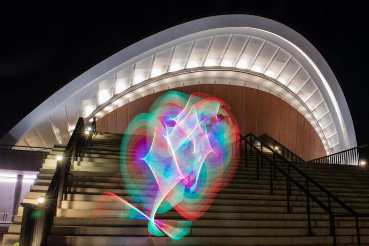 Ort der Festlichkeiten: Ein Mann zeichnet mit einem Lichtstab vor dem Haus der Kulturen der Welt Muster in den Abendhimmel.