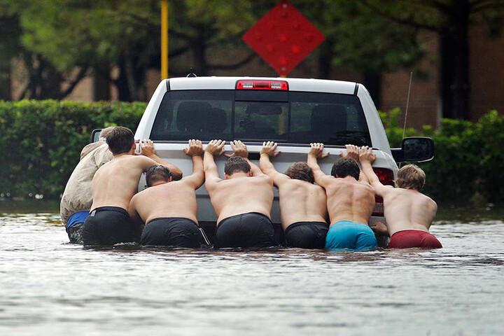Sechs Männer schieben einen Kleintransporter über eine überflutete Straße.