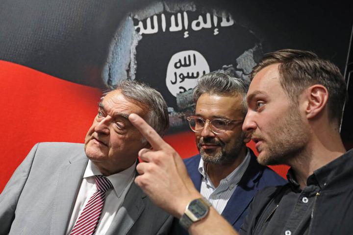 Herbert Reul (CDU, l-r), Innenminister von Nordrhein-Westfalen, Alexander Wipprecht und Orlando Klaus, Filmproduzenten der Firma BlueLaserBoys, sprechen auf dem Stand des Landesverfassungsschutzes auf der Gamescom miteinander.