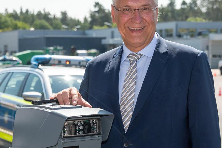 Joachim Herrmann (CSU), bayerischer Innenminister, steht an einer transportablen automatisierten Kennzeichenerkennungs-Anlage (AKE).