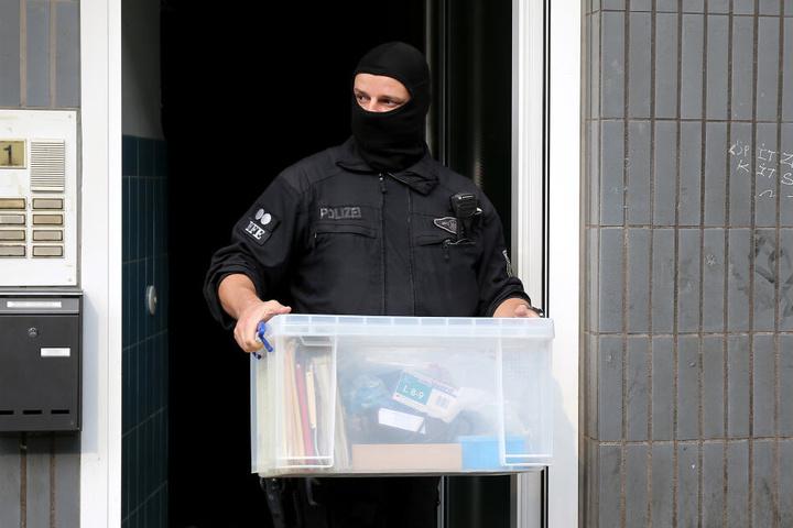 Ein Bundespolizist verlässt ein Wohnhaus mit sichergestelltem Material.