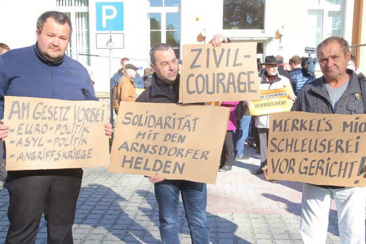 Marco Wruck (links, NPD) hat sich vor dem Kamenzer Gericht mit Schildern postiert.