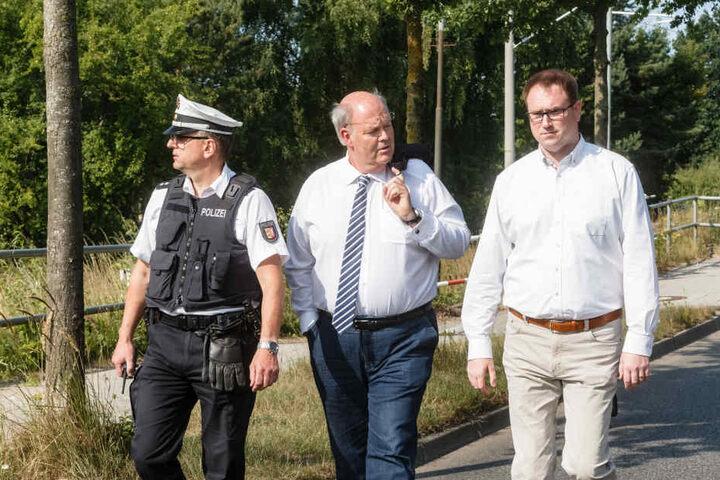 Hans-Joachim Grote (Innenminister Schleswig Holsteins, CDU) (mitte) und Jan Lindenau (Bürgermeister von Lübeck, SPD) (rechts) gehen mit einem Polizeivertreter zum Tatort.