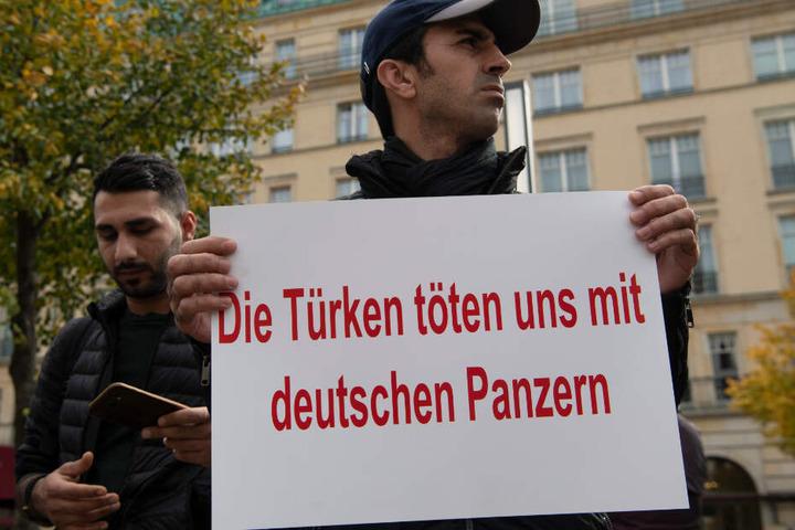 """Ein Demonstrant hält bei einer Protestaktion gegen die türkische Militäroffensive in Nordsyrien am Pariser Platz ein Plakat mit der Aufschrift """"Die Türkei tötet uns mit deutschen Panzern""""."""