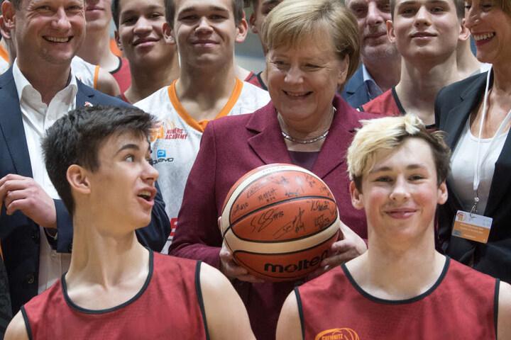 Micaela Schönherr (r.), Präsidentin des Basketball-Zweitligisten Niners Chemnitz, Bundeskanzlerin Angela Merkel (CDU) und Steffen Herold, Geschäftsführer der Niners, unterhalten sich beim Training des Nachwuchsteams des Basketball-Vereins in Chemnitz mit