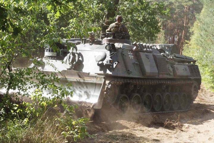 Damit die Feuerwehrleute besser an die Glutnester herankommen, schneidet ein Panzer der Bundeswehr eine Schneise in den Wald.