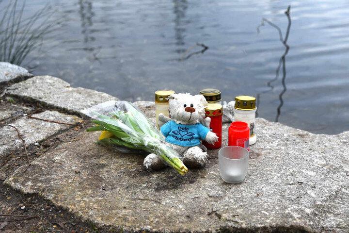 Jemand hat Kerzen, Blumen und ein Stofftier am Ufer des Weihers abgelegt.