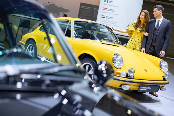 Die Models Vivien und Olaf posieren bei der Techno Classica für Oldtimer und Youngtimer vor einem Porsche 911 aus dem Jahr 1968.