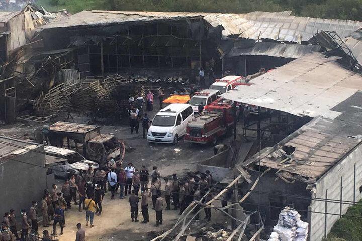 Polizisten und Rettungskräfte untersuchen Tangerang (Indonesien) die  zerstörte Feuerwerksfabrik.