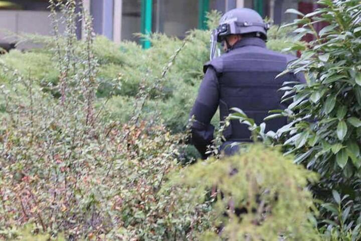 Ein Polizist in Schutzanzug durchsucht das Gebüsch vor dem Haus der Presse.