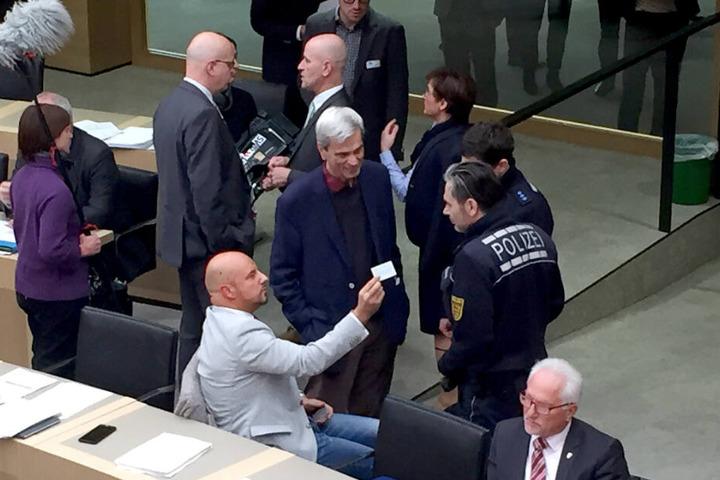 Stefan Räpple (sitzend, l.), Abgeordneter der AfD im Landtag von Baden-Württemberg und der fraktionslose AfD-Politiker Wolfgang Gedeon (Mitte) sprechen während einer Plenarsitzung mit Polizisten.
