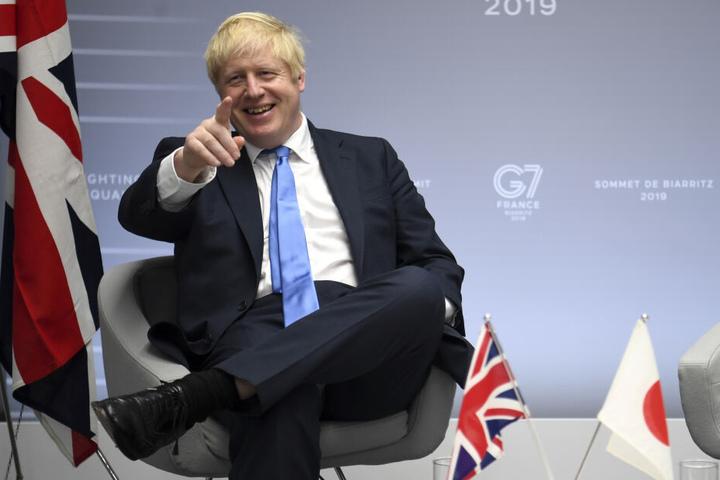 Boris Johnson breit grinsend beim G7 Gipfel.