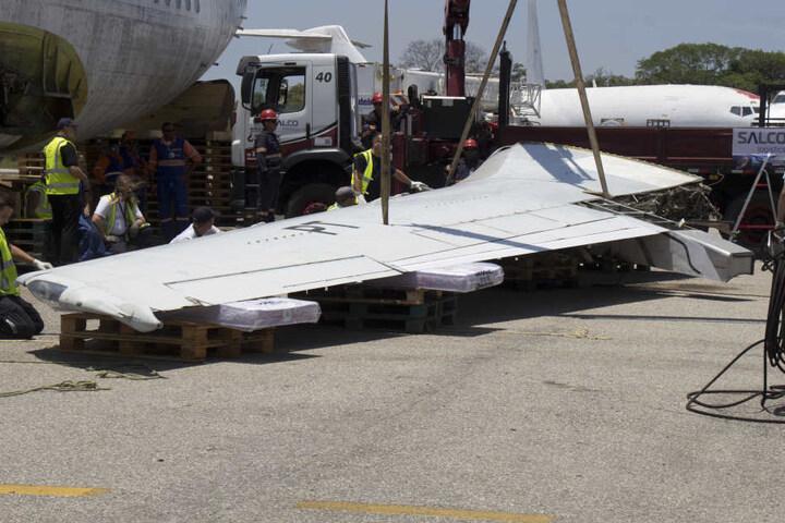 Monteure nehmen den linken Flügel der Maschine ab.