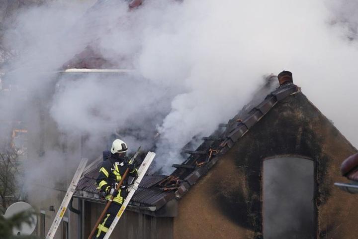 Ein Feuerwehrmann bekämpfte auf dem Schuppendach das Feuer.