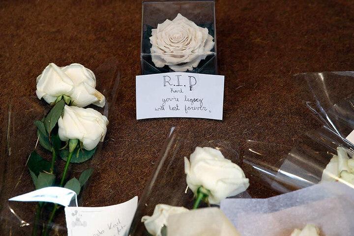Blumen und ein Zettel liegen am Eingang der Chanel-Zentrale in Paris. Sie wurden von Passanten dort abgelegt, um dem verstorbenen Modeschöpfer Karl Lagerfeld zu gedenken.