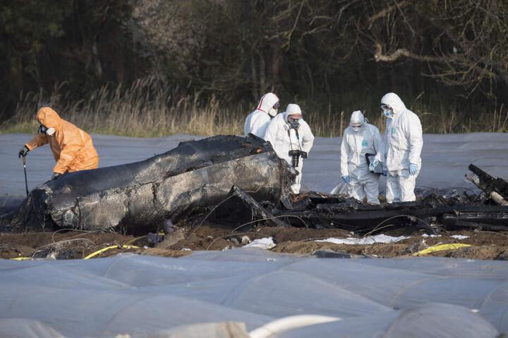 Einsatzkräfte untersuchen das Flugzeug-Wrack am Absturzort.