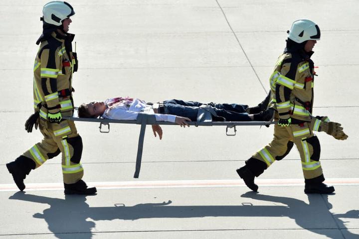 """Rettungskräfte transportieren einen """"Verletzten"""" ab."""