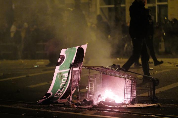 An dem brennenden Einkaufswagen hing ein auf eine Pappe gemaltes Polizeifahrzeug.