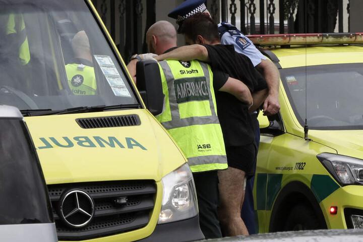 Ein Polizist und Rettungskräfte helfen einem Verwundeten außerhalb einer Moschee.