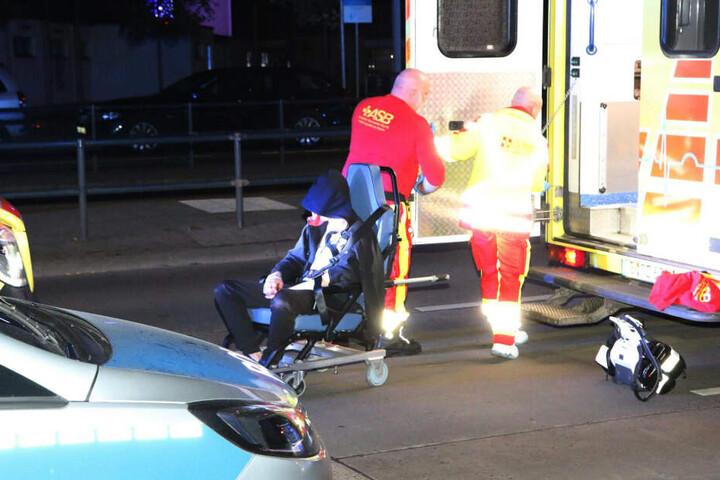Ein Verletzter wird von Notfallsanitätern in ein Einsatzfahrzeug geladen.