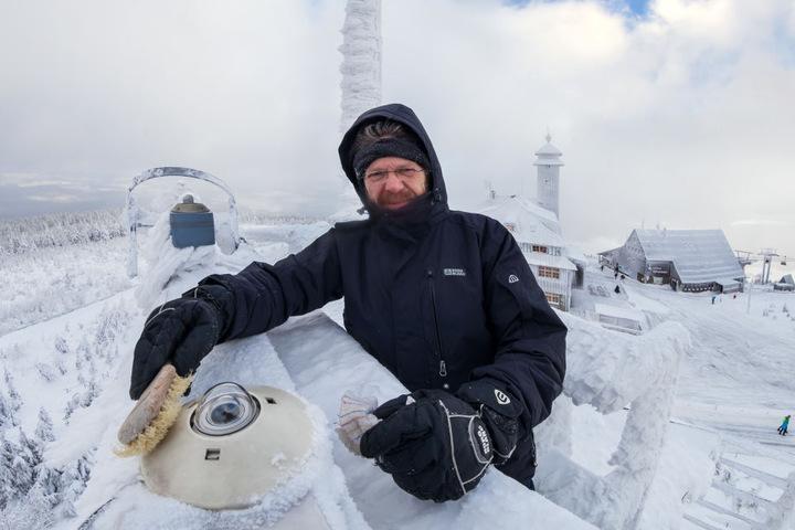Gerd Franze, Leiter der Wetterwarte befreit ein Messgerät vom Schnee.