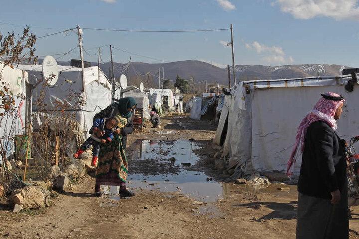 Syrische Flüchtlinge gehen durch ein Flüchtlingslager in der Bekaa-Ebene.