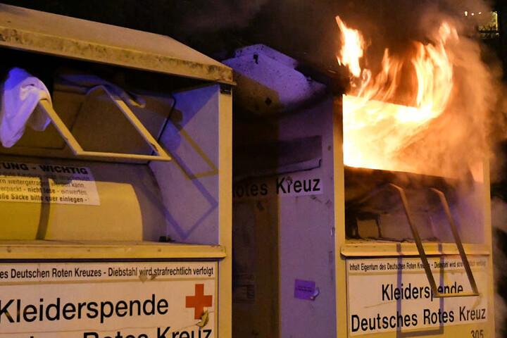 Das Foto zeigt einen Altkleidercontainer, aus dem Flammen heraus lodern.