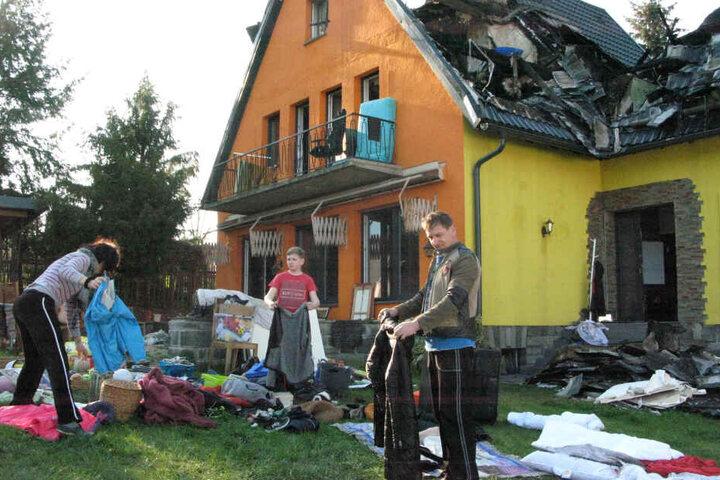 Aufräumen nach der Brandkatastrophe: Sergey (46), Natalie (43) und Sohn Philipp (13) lüften ihre verqualmte Kleidung.