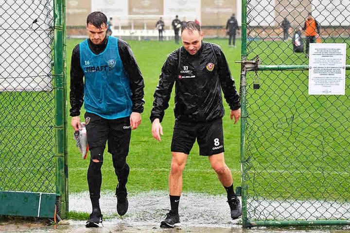 Patschnass! Philip Heise (l.) und Rico Benatelli verlassen den Trainingsplatz.